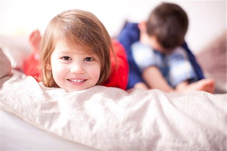 Portrait of young girl smiling and brother sulking Stock Photo - Premium Royalty-Free, Code: 649-07063624