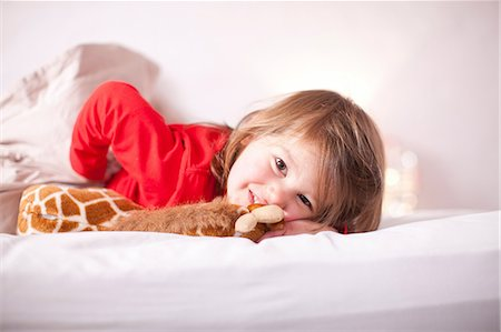 Young girl lying on bed with toy giraffe Stock Photo - Premium Royalty-Free, Code: 649-07063622