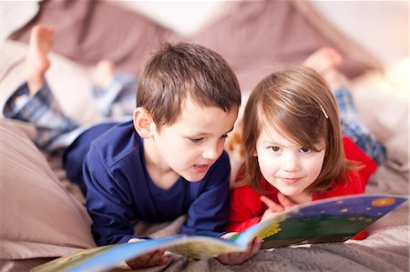 Two young children lying on bed looking at picture book Stock Photo - Premium Royalty-Free, Code: 649-07063623