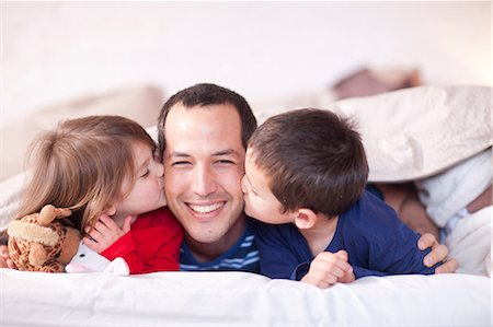 Son and daughter kissing fathers cheek under duvet Stock Photo - Premium Royalty-Free, Code: 649-07063634