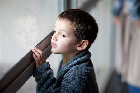 Young boy watching through porch window Stock Photo - Premium Royalty-Free, Code: 649-07063637