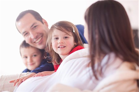 expectation - Parents and young two children lounging on bed Stock Photo - Premium Royalty-Free, Code: 649-07063631