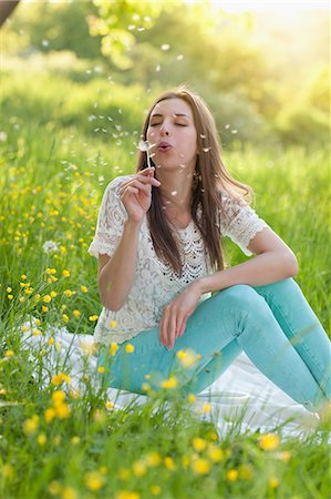 Young woman sitting in meadow blowing dandelion clock Stock Photo - Premium Royalty-Free, Code: 649-07063645