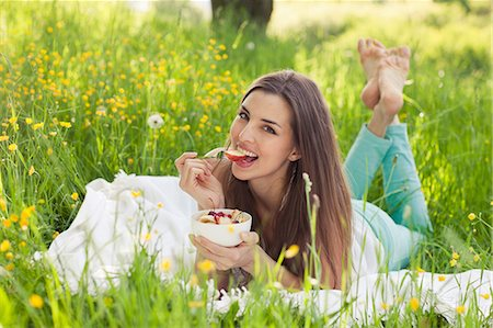 Woman in field of buttercups eating fresh fruit Stock Photo - Premium Royalty-Free, Code: 649-07063652