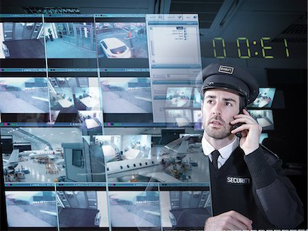 Security guard monitoring camera visuals on interactive screen Stock Photo - Premium Royalty-Free, Code: 649-07063668