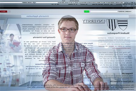 Young student looking at university prospectus on screen Stock Photo - Premium Royalty-Free, Code: 649-07063669