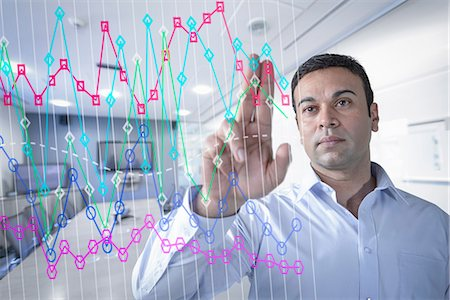 Businessman in office using interactive screen Stock Photo - Premium Royalty-Free, Code: 649-07063661