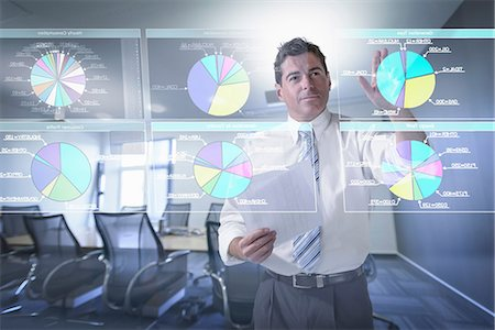 Businessman looking at pie charts on interactive screen Stock Photo - Premium Royalty-Free, Code: 649-07063662