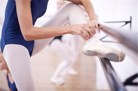 preteen girls stretching - Ballerina fastening ballet slipper at the barre Stock Photo - Premium Royalty-Free, Code: 649-07063708
