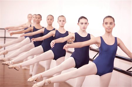 preteen girls stretching - Row of teenage ballerinas with legs outstretched Stock Photo - Premium Royalty-Free, Code: 649-07063714