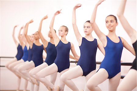 preteen girls stretching - Row of teenage ballerinas with arms outstretched Stock Photo - Premium Royalty-Free, Code: 649-07063715