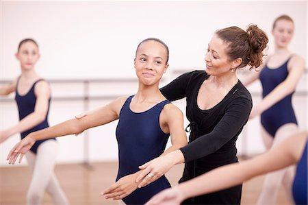 Teacher adjusting arms of shy teenage ballerina Stock Photo - Premium Royalty-Free, Code: 649-07063721