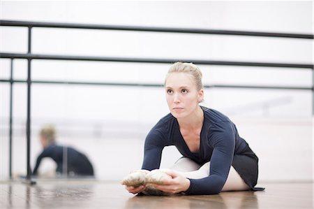 Female ballerina stretching on the floor Stock Photo - Premium Royalty-Free, Code: 649-07063739
