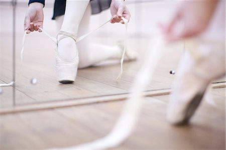 Ballerina putting on ballet slippers Stock Photo - Premium Royalty-Free, Code: 649-07063745