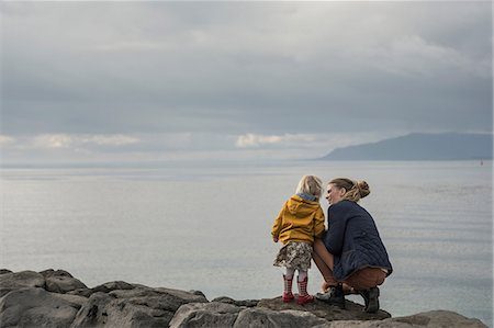 Mother and toddler crouching on harbor wall Stock Photo - Premium Royalty-Free, Code: 649-07063828