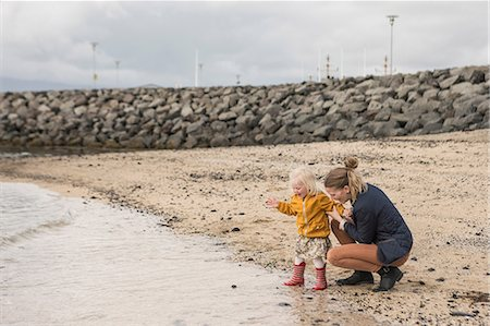 Mother and toddler crouching at waters edge Stock Photo - Premium Royalty-Free, Code: 649-07063821