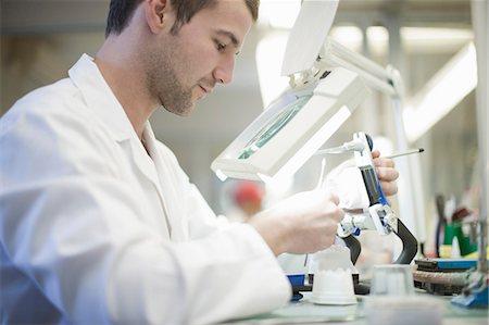 dentistry - Dental technician using magnifier to repair denture Stock Photo - Premium Royalty-Free, Code: 649-07063851