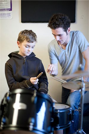 Young male teaching boy how to hold drumsticks Stock Photo - Premium Royalty-Free, Code: 649-07063860