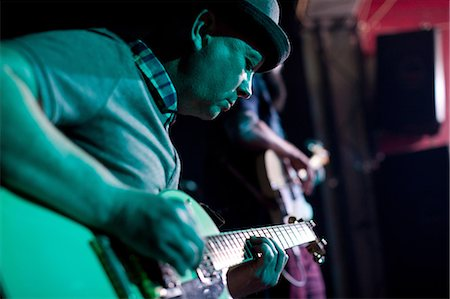 Man playing guitar on stage in nightclub Stock Photo - Premium Royalty-Free, Code: 649-07063898