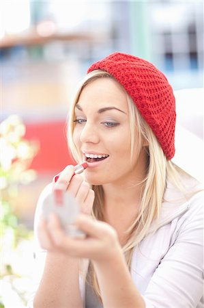 red - Young woman in red knitted hat applying lipstick Stock Photo - Premium Royalty-Free, Code: 649-07063925