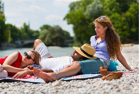 Three friends relaxing by Isar River, Munich, Germany Stock Photo - Premium Royalty-Free, Code: 649-07118239