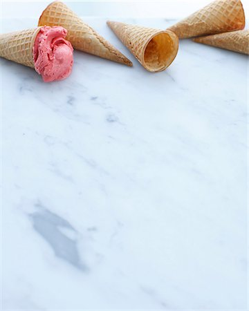 Still life of empty cones and one with scoop of strawberry ice cream Stock Photo - Premium Royalty-Free, Code: 649-07118273