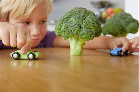 Boy playing cars around broccoli trees Stock Photo - Premium Royalty-Free, Code: 649-07118288
