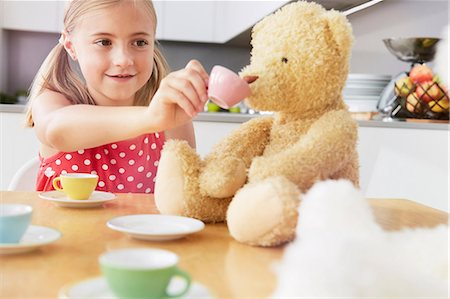 Girl having tea party with soft toys Stock Photo - Premium Royalty-Free, Code: 649-07118298