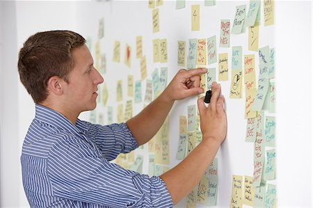 self adhesive note - Young man sticking adhesive note on wall Stock Photo - Premium Royalty-Free, Code: 649-07118375