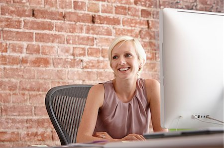 portrait looking away - Portrait of mid adult woman at desk with brick wall Stock Photo - Premium Royalty-Free, Code: 649-07118378