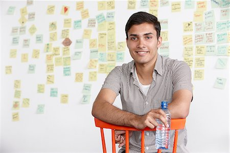 Portrait of young man with adhesive notes in background Stock Photo - Premium Royalty-Free, Code: 649-07118372