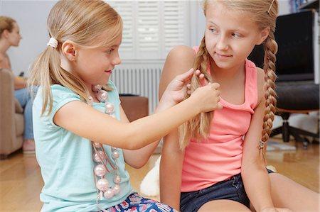preteen beauty - Girl plaiting sister's hair Stock Photo - Premium Royalty-Free, Code: 649-07118393