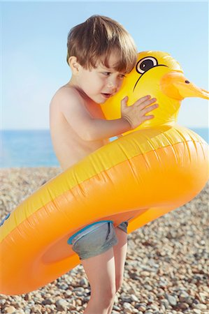 safety - Boy hugging duck shaped float Stock Photo - Premium Royalty-Free, Code: 649-07118506