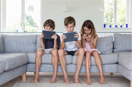 preteen boys playing - Brothers and sister on sofa with digital tablets and mobile Stock Photo - Premium Royalty-Free, Code: 649-07118650