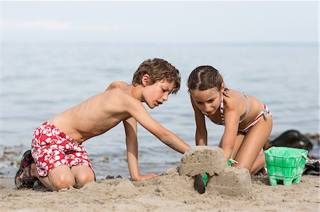 Brother and sister on beach building sandcastle Stock Photo - Premium Royalty-Free, Code: 649-07118653