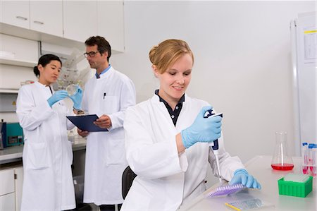 results - Group of scientists working in laboratory. Pipetting solution into microtiter plate (front), discussing bacterial growth on petri dish (back) Stock Photo - Premium Royalty-Free, Code: 649-07118830