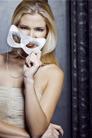 Portrait of young woman holding feline mask Stock Photo - Premium Royalty-Free, Code: 649-07118850