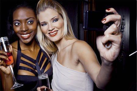 Two female friends making self portrait in nightclub Stock Photo - Premium Royalty-Free, Code: 649-07118904