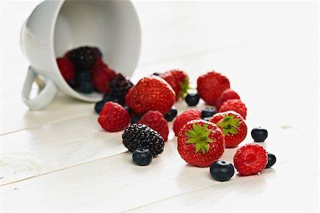 strawberries - Strawberries, raspberries, blackberries and blueberries spilling form teacup Stock Photo - Premium Royalty-Free, Code: 649-07119019