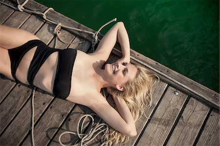 Young woman sunbathing on pier Stock Photo - Premium Royalty-Free, Code: 649-07119036