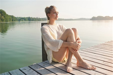 Young woman sitting on lake pier Stock Photo - Premium Royalty-Free, Code: 649-07119055