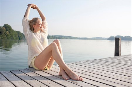 Young woman relaxing on lake pier Stock Photo - Premium Royalty-Free, Code: 649-07119056