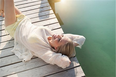 Young woman sunbathing on lake pier Stock Photo - Premium Royalty-Free, Code: 649-07119058