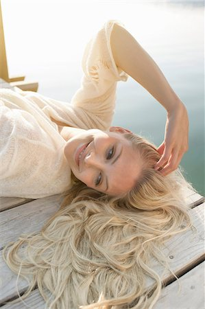 sweater - Young woman lying on lake pier Stock Photo - Premium Royalty-Free, Code: 649-07119059