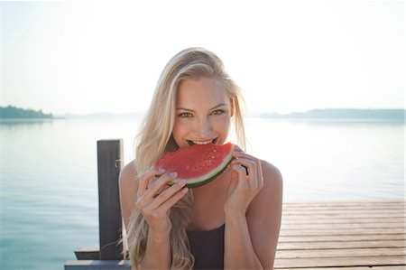 delicious - Portrait of young woman at lake eating watermelon Stock Photo - Premium Royalty-Free, Code: 649-07119051
