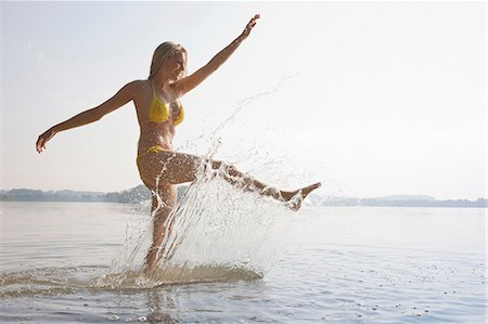 Young woman kicking water in lake Stock Photo - Premium Royalty-Free, Code: 649-07119063