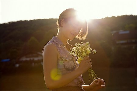 femininity - Young woman in meadow holding bunch of wild flowers Stock Photo - Premium Royalty-Free, Code: 649-07119077
