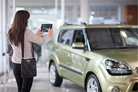 Mid adult woman taking photograph of car in showroom Stock Photo - Premium Royalty-Free, Code: 649-07119124