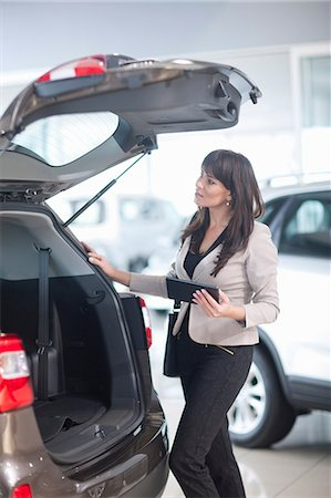 Mid adult woman checking car boot in showroom Stock Photo - Premium Royalty-Free, Code: 649-07119127