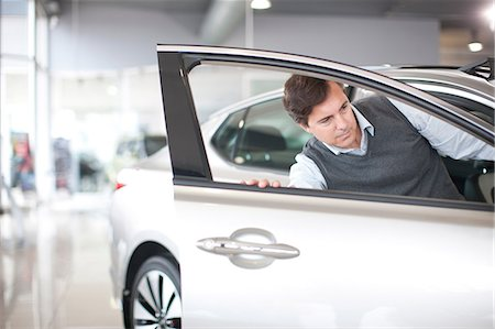Mid adult man checking door in car showroom Stock Photo - Premium Royalty-Free, Code: 649-07119135